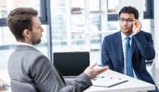 Two businessmen in formal wear sitting and talking at job interview, business concept